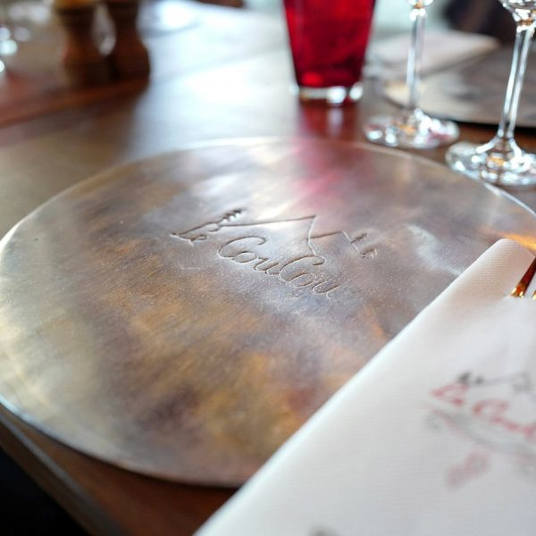 A metal tray, glasses and fork on the table of Le Coucou Restaurant in Montreux.