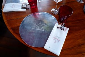 Knife, fork, glasses and metal tray on the table of Le Coucou Restaurant in Montreux.
