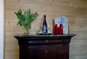 Vase with flowers, bottle of wine and books on chest of drawers at the Le Coucou Hotel.