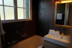 Wash basin, mirror, bathtub and window at the bathroom of Le Coucou Hotel and Restaurant in Montreux