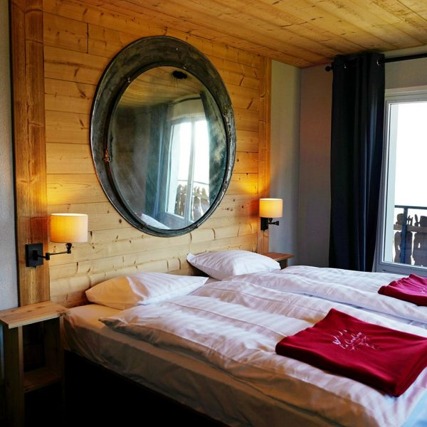 Red blankets with the logo of the Le Coucou Hotel on two single beds and a mirror above the beds.
