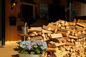 Purple geranium and wood for the fireplace outside the Le Coucou Hotel and Restaurant.