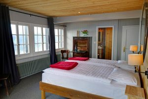 Double bed, wall lamps, chest of drawers and window at the Le Coucou Hotel and Restaurant.
