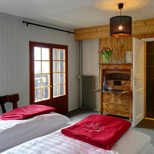 Two single beds, an elegant chests of drawers and view of the bathroom at a room of Le Coucou.