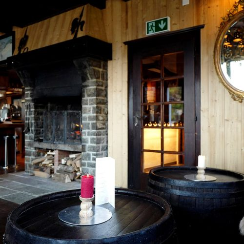 Candles and candlesticks on barrels, mirror and a fireplace at Le Coucou Mountain Bar.