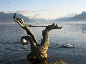 Statue of Hippocampus in the Lake Geneva. A white swan in the lake and view of the Alps.