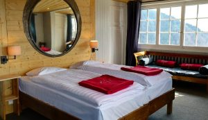 Two single beds, a round mirror and a sofa at a bedroom of Le Coucou Hotel with view on Lake Geneva.