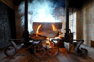 Fire in a fireplace at the Le Coucou Restaurant, where anyone can taste Swiss specialities