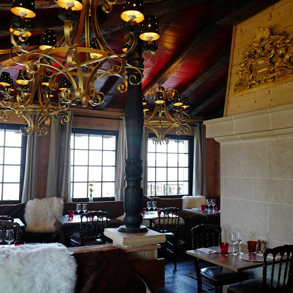 Chandelier, dining tables and elegant chairs at Le Coucou Restaurant in Montreux.