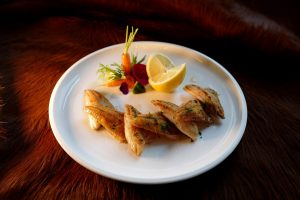 Fish served with vegetables at Le Coucou Restaurant. Cuisine made with high quality products.