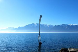 A huge fork in the Lake Geneva and view of the Alps in Montreux, Switzerland.