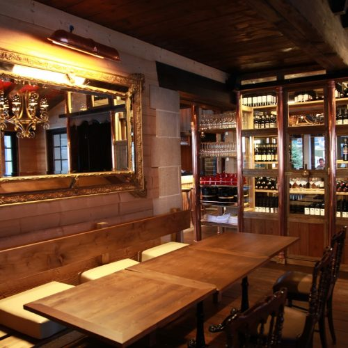 Tables, seats, mirror and shelves with wine and champagnes bottles at the Le Coucou Restaurant.