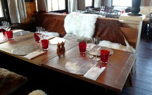 Wooden tables, warm fleece on a bench and stylish glasses at Le Coucou Restaurant above Montreux
